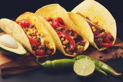 Drie Mexicaanse taco's met fijngehakte rundvlees en mengelingsgroenten op een zwarte achtergrond Mexicaanse schotel met avocado K Royalty-vrije Stock Foto