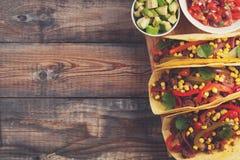 Drie Mexicaanse taco's met fijngehakte rundvlees en mengelingsgroenten op oude rustieke lijst Mexicaanse schotel met sausensalsa  Royalty-vrije Stock Afbeeldingen