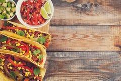 Drie Mexicaanse taco's met fijngehakte rundvlees en mengelingsgroenten op oude rustieke lijst Mexicaanse schotel met sausensalsa  Royalty-vrije Stock Foto