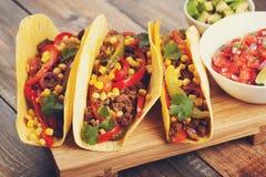 Drie Mexicaanse taco's met fijngehakte rundvlees en mengelingsgroenten op oude rustieke lijst Mexicaanse schotel met sausensalsa  Stock Afbeelding