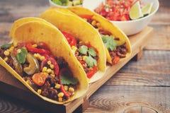 Drie Mexicaanse taco's met fijngehakte rundvlees en mengelingsgroenten op oude rustieke lijst Mexicaanse schotel met sausensalsa  Stock Fotografie