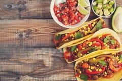 Drie Mexicaanse taco's met fijngehakte rundvlees en mengelingsgroenten op oude rustieke lijst Mexicaanse schotel met saussalsa in Royalty-vrije Stock Afbeelding
