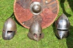 Drie middeleeuwse ridder` s helmen en rond houten schild Royalty-vrije Stock Afbeelding