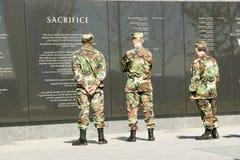 Drie militairen bekijken granietinschrijving op muur van Het Gedenkteken van de Luchtmacht, Arlington, Virginia op het gebied van royalty-vrije stock fotografie