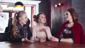 Drie modieuze huisvrouwen die een rust in een bar hebben, cocktails drinken en aan elkaar, het gekscheren spreken Gelukkige tijd stock footage