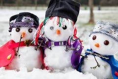 Drie modieuze prachtig geklede sneeuwmannen Stock Afbeelding
