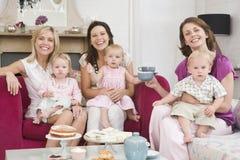 Drie moeders in ruimte met babys en koffie Stock Foto