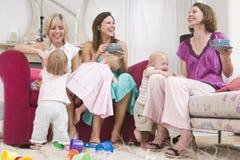 Drie moeders in ruimte met koffie en babys Royalty-vrije Stock Afbeeldingen