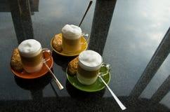 Drie mokken met koffie en room op opmaker Stock Foto's