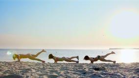 Drie mooie, atletische vrouwen, in zwempakken, die opdrukoefeningen doen, oefent synchroon uit Voor het strand, in de zomer, bij stock footage