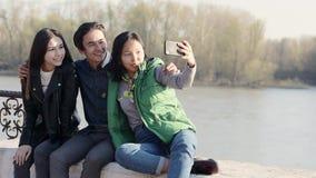 Drie mooie Aziatische tieners die een grappige selfie met hun smartphone nemen stock videobeelden