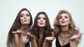 Drie mooie en modieuze meisjes die met make-up lucht kus en het glimlachen verzenden stock footage