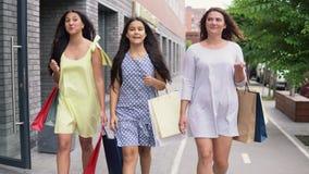 Drie mooie jonge meisjes lopen onderaan de straat met pakketten in hun handen na het winkelen, hebbend een goede stemming 4K stock videobeelden