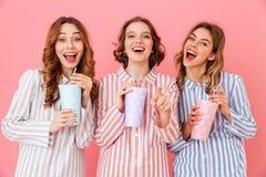 Drie mooie jonge meisjesjaren '20 die kleurrijke gestreepte pyjama dragen Stock Fotografie