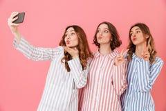 Drie mooie jonge meisjesjaren '20 die kleurrijke gestreepte pyjama Ha dragen Stock Afbeelding