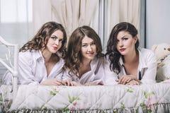 Drie mooie jonge vrouwenvrienden die in de slaapkamer binnen babbelen stock foto's