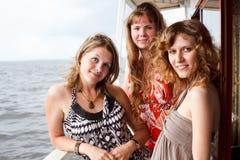 Drie mooie jonge wijfjes op dek van schip Royalty-vrije Stock Foto's