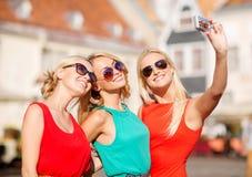 Drie mooie meisjes die beeld in de stad nemen Royalty-vrije Stock Foto's