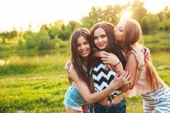 Drie mooie meisjes die en op zonsondergang in het park lopen lachen Het concept van de vriendschap Stock Foto