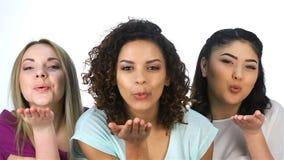 Drie mooie meisjes die kussen blazen stock footage