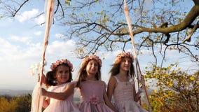 Drie mooie meisjes die op een schommeling onder een grote boom slingeren stock footage