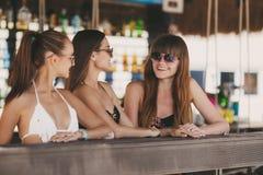 Drie mooie meisjes in een bar op het strand Stock Fotografie