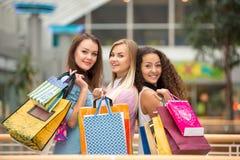 Drie mooie meisjes met het winkelen zakken Stock Afbeeldingen