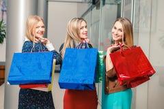 Drie mooie meisjes met het winkelen zakken Stock Foto