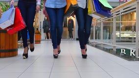 Drie mooie meisjes met het winkelen zakken gaat  stock video