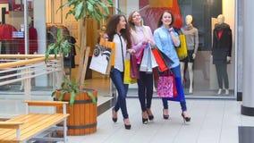 Drie mooie meisjes met het winkelen zakken gaat  stock footage