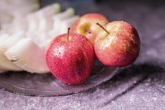 Drie mooie rode appelen en een meloen op een plaat stock afbeeldingen