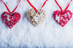 Drie mooie romantische uitstekende harten hangen op een rode band op een witte sneeuwachtergrond Liefde en St het concept van de  Stock Afbeeldingen