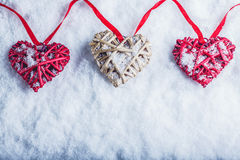 Drie mooie romantische uitstekende harten hangen op een rode band op een witte sneeuwachtergrond Liefde en St het concept van de  stock foto's