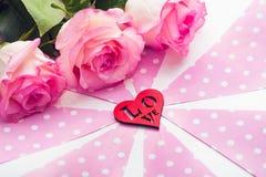 Drie mooie rozen en rood cijfer van hart op roze witte achtergrond St de Dag van de valentijnskaart ` s stock afbeelding