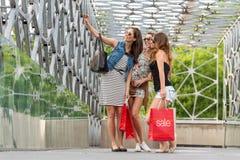 Drie mooie vrouw op de brug, hand - gehouden het winkelen zakken Royalty-vrije Stock Afbeeldingen