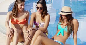Drie mooie vrouwen die bij een zwembad ontspannen stock footage