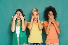 Drie mooie vrouwen die bij groene achtergrond stellen royalty-vrije stock afbeeldingen