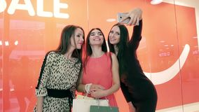 Drie mooie vrouwen die voor een gezamenlijke foto in winkelcentrum stellen stock footage
