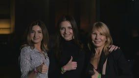 Drie mooie vrouwen toont een duim in de camera stock video