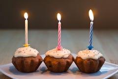 Drie muffins met het branden van kaarsen Royalty-vrije Stock Afbeeldingen