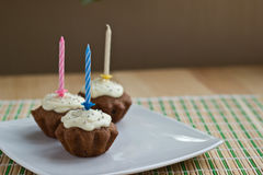Drie muffins met kaarsen Stock Afbeeldingen