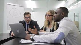 Drie multi-etnische collega's bespreken digitale munt marcet sutiation in het bureau stock video