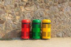 Drie multicolored kringloopbakken voor afval dichtbij de muur Soortafval stock afbeeldingen
