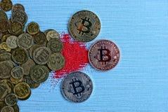 Drie muntstukken bitcoin op een blauwe lijst en een rood zand bij een stapel van muntstukken Royalty-vrije Stock Afbeelding