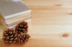 Drie natuurlijke denneappels en stapel boeken op lichtbruine houten lijst, met vrije ruimte voor ontwerp Stock Foto's