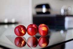 Drie nectarines op de glaslijst Royalty-vrije Stock Afbeeldingen