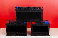 Drie nieuwe zwarte navulbare batterijen bevinden zich piramide op elkaar op een rode achtergrond met witte inschrijvingen De auto royalty-vrije stock foto's