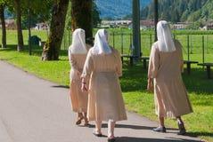 Drie nonnen die op een asfaltweg lopen stock afbeelding