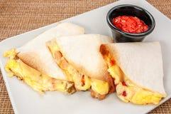 Drie omslagen van burritoburritos met rundvlees en groenten op witte plaat met rode saus stock afbeelding