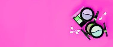 Drie Oogschaduwwenpallets en instrumenten op heldere roze achtergrond royalty-vrije stock afbeeldingen